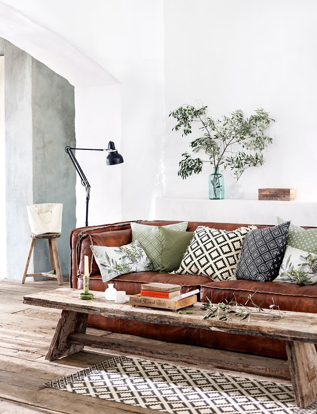 Rustikale Wohnzimmergestaltung Couchtisch Hocker Teppich Ledersofa Stehlampe Holzbank Sofa