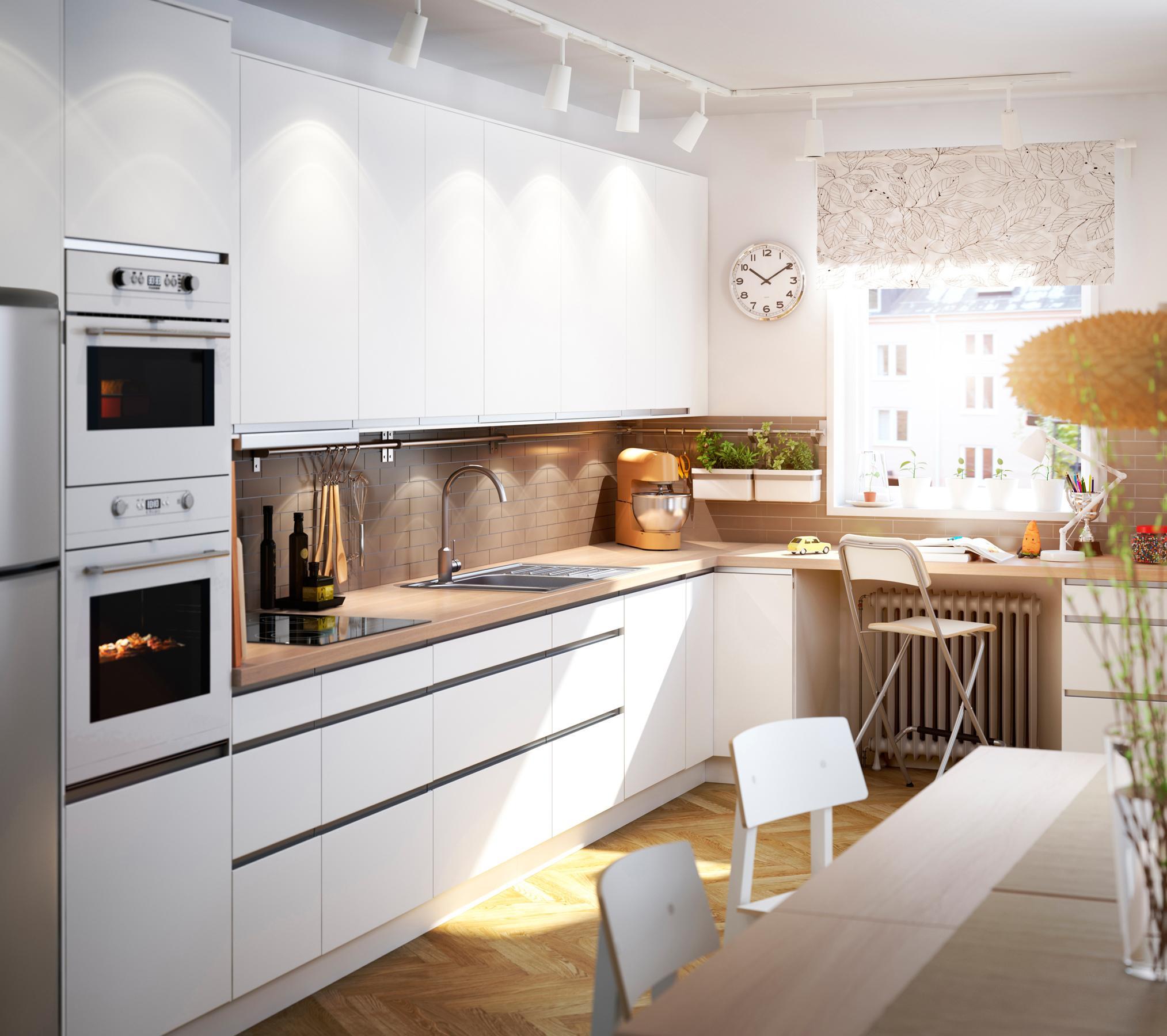 Weiße Einbauküche und Essbereich im natürlichen Look...